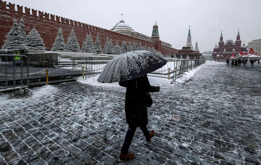 FOTO: Una mujer camina en la Plaza Roja pasando el Kremlin después de una noche de fuertes nevadas en Moscú, el 6 de diciembre de 2018.