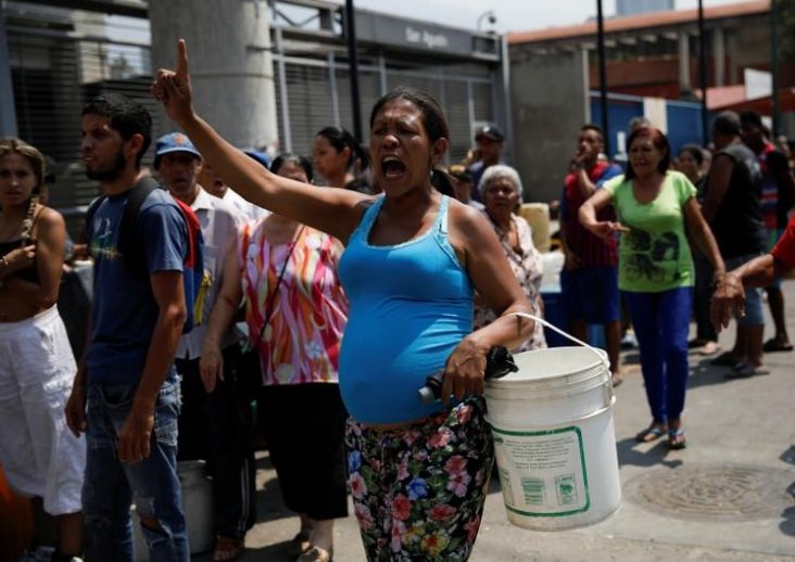 Personas gritan en la calle mientras se reúnen para recolectar agua en Caracas, Venezuela. 1 de abril de 2019