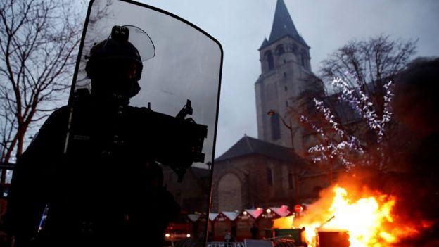 """El fuego se ve cerca de un mercado navideño durante una manifestación del movimiento """"chalecos amarillos"""" en el Boulevard Saint Germain en París, Francia, el 5 de enero de 2019."""