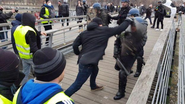 """Un hombre en una posición de boxeo lucha contra la policía antidisturbios durante una manifestación de manifestantes antigubernamentales """"Gilets Jaunes"""" en un puente que conduce a la Asamblea Nacional en París el 5 de enero de 2019."""